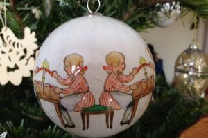 close-up of christmas tree bauble with image of young girl lighting a candle
