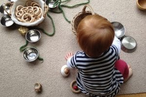 toddler sitting on rug back to camera looking at variety of toys