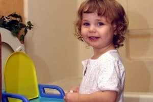 toddler standing next to toilet training seat and smiling at camera