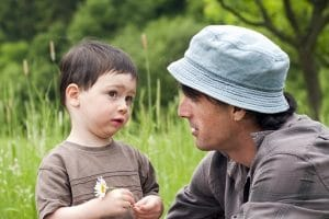 Dad in hat talking to young boy holding a daisy and not meeting dad's eye