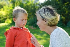 Mum staring at and pointing her finger at toddler in orange hoodie looking upset