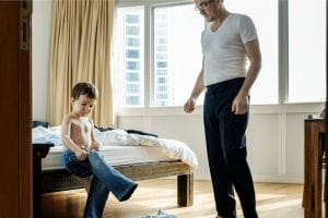 Dad standing over child in bedroom as child puts on his jeans
