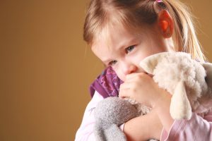 young girl cuddling soft toy and looking anxious