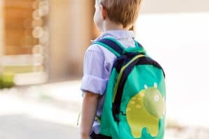 young boy in school uniform wearing back pack on his way to school