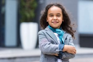 young girl in smart jacket and scarf arms folded looking confident