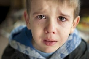 young boy in hoodie staring at camera with tears on his cheeks and crying
