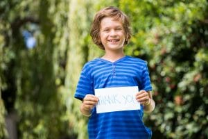 young boy in blue striped t-shirt smiling and holding up hand written sign saying Thank You
