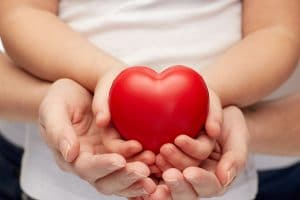 adult hands supporting child's hands holding a heart shaped object