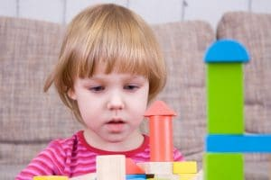 young boy looking intently as a set of toy building blocks