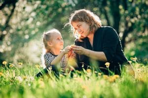 Mum looking intently at daughter as they examine a wildflower