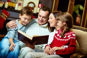 Mum, dad and two children sitting on sofa enjoying a book at Christmas