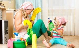 Mum and little girl ready for housework sitting on floor both having fun