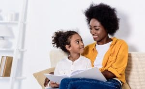 Mum and daughter sitting in armchair reading a book both smiling