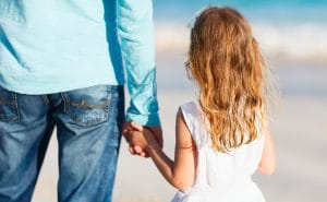 young girl holding dad's hand back to camera