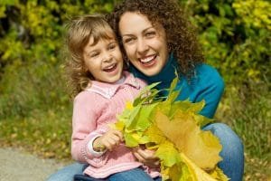 Mum and daughter cuddling and smiling while holding a bunch of leaves