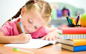 young girl with plaits writing in notebook and smiling