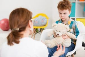 young boy with teddy sitting on chair looking angry at adult talking to him