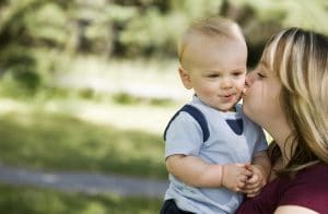Mum giving young son a kiss on the cheek son smiling