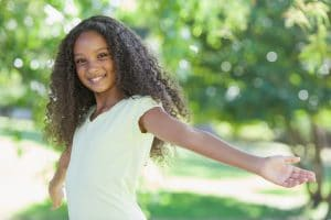 young girl long dark curly hair smiling arms aoutstretched