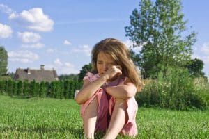 young girl sitting on grass crying having tantrum