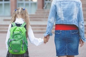 mum holding girl's hand going back to school backs to camera