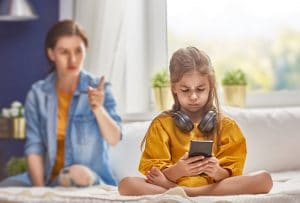 young girls with mobile phione scowling ignoring parent back turned