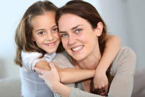 mum and daughter cuddling and smiling at the camera