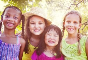 four young girls smiling at the camera in sunshine practical parenting