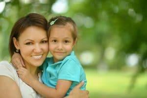 mother hugging little girl smiling happy family